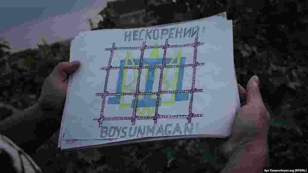 Стилизованный украинский тризуб и крымскотатарская тамга за условной решеткой