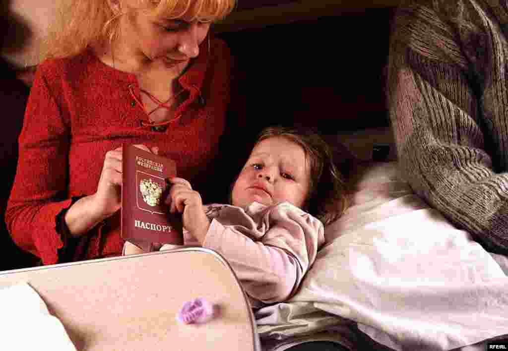 Diana from Kaliningrad comforts her daughter Arina as the train approaches the Russian border and Kaliningrad.
