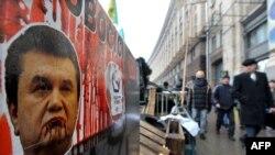 Люди идут мимо плаката с изображением президента Украины Виктора Януковича. Киев, 16 декабря 2013 года.