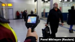 Проверка температуры тела у пассажиров, прибывающих в международный аэропорт Алматы. 21 января 2020 года.