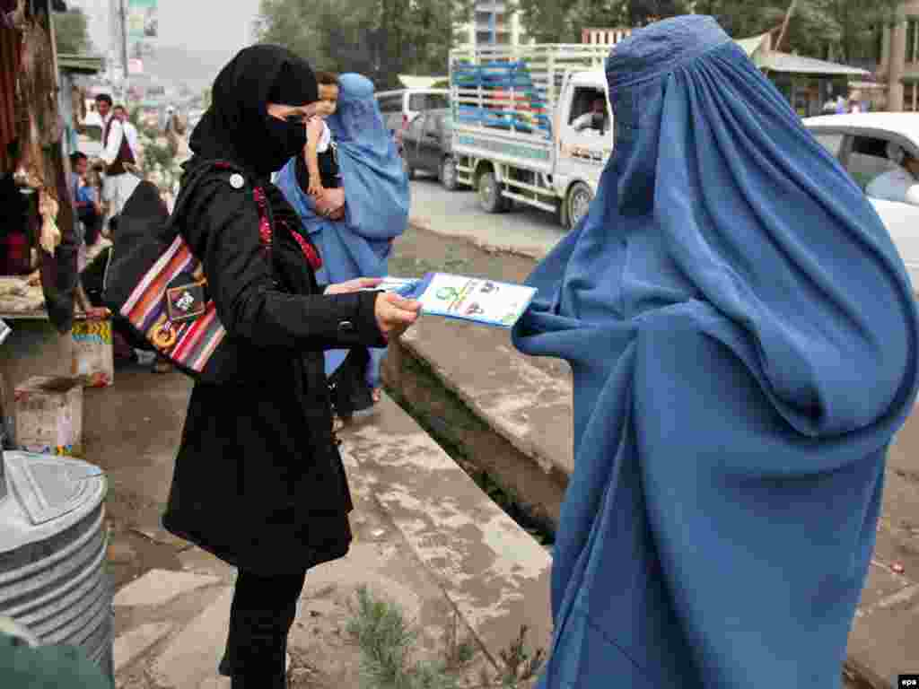 Afghanistan -- A woman distributes leaflets illustrating vote casting in Kabul, 03Aug2010