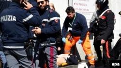 Спасатели и полицейские выносят из здания пострадавшего
