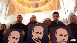 Сербские сторонники Владимира Путина стоят с его портретами в церкви в Белграде.