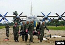 Офіцери українських військово-повітряних сил несуть тіло людини, яка загинула в результаті падіння винищувача