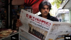 An Iranian man reads a copy of the 'Hamshahri' newspaper, featuring a picture of Iranian foreign minister Mohamad Javad Zarif and his counterparts from France, Germany, UK, China, Russia and the US, outside a kiosk in Tehran, 25 November 2014.