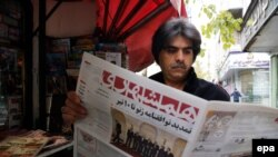 An Iranian man reads a copy of the 'Hamshahri' newspaper outside a kiosk in Tehran. File photo