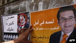 An Egyptian puts up campaign posters ahead of this year's presidential election.