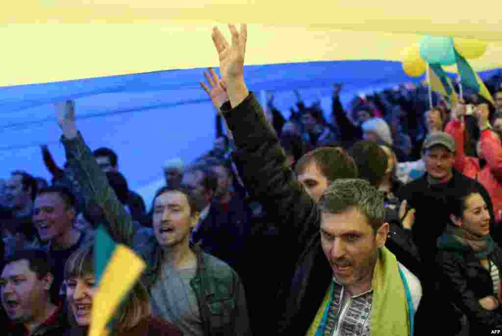 Ukrainians hold up a large national flag and shout slogans as they take part in a nationalist and pro-unity rally in the eastern city of Donetsk.(AFP/Anatoly Stepanov)