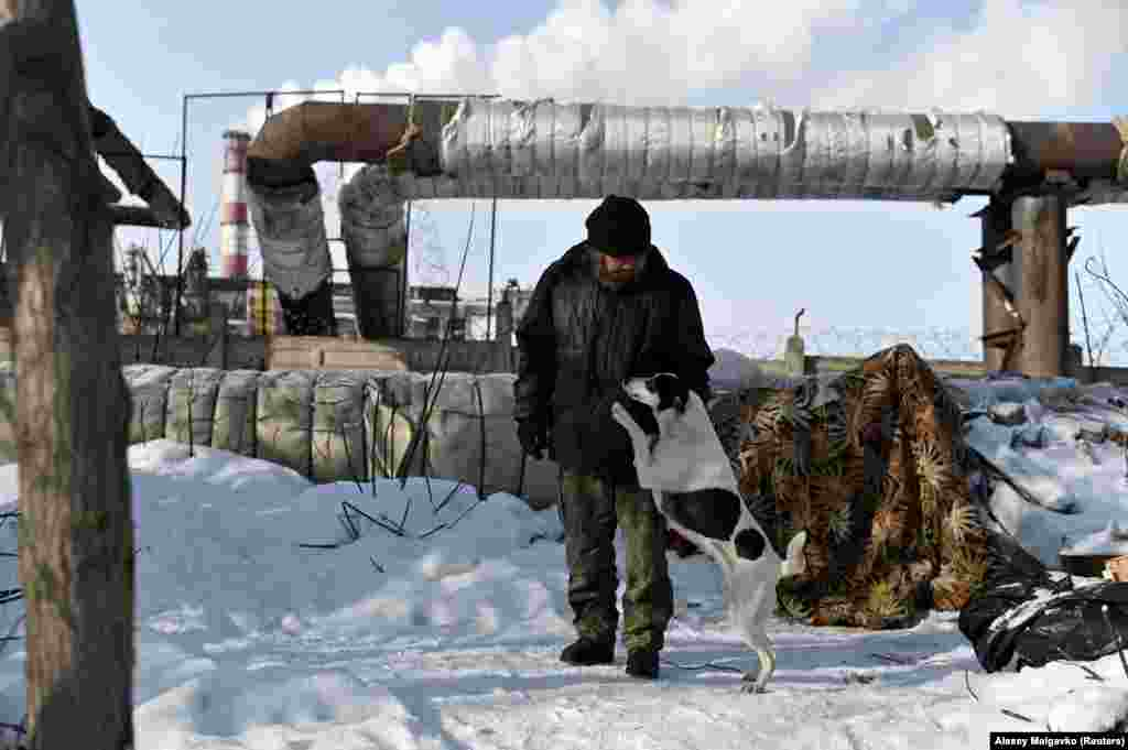 """Aleksei Vergunov, 46, nicknamed """"Lyokha Boroda"""" (Lyokha the Beard), stands near his makeshift shelter with his dog, Bella. He worries that -- in the haze of hard alcohol he drinks to keep warm and dull reality -- he might get severe burns by sleeping too close to the pipe."""
