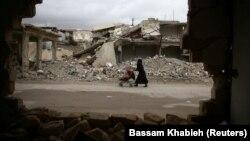 Женщина с ребенком среди руин в сирийском городе.