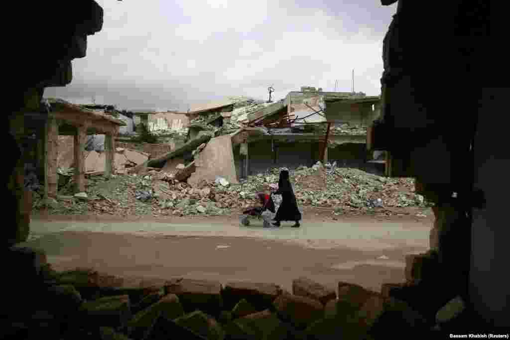 Жанчына зь дзіцячым вазком у зьнішчаным квартале Дамаску.