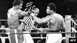 Le champion du monde de boxe des poids lourds américain George Foreman (G) et son compatriote Mohamed Ali (Cassius Clay) (D) combattent à Kinshasa, le 30 octobre 1974, lors du match à l'issu duquel Mohamed Ali, reprenant l'offensive, regagnera son titre d