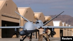U.S. airmen prepare a US Air Force MQ-9 Reaper drone as it leaves on a mission at Kandahar Air Field in March.