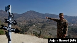 A Pakistani Army officer points out the site where an Indian fighter jet was shot down and its pilot, Wing Commander Abhinandan Varthaman, was captured, during an event in Horran village, near the Line of Control.