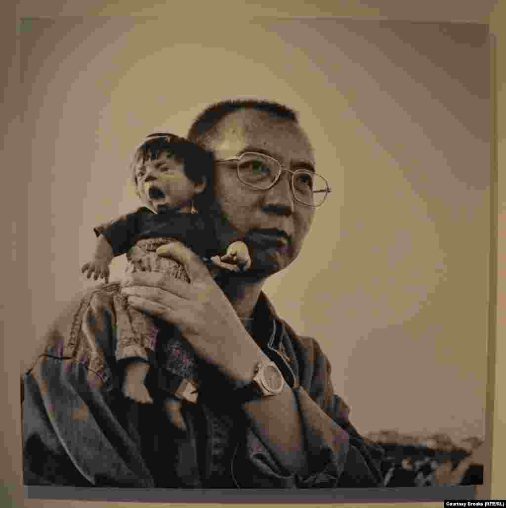 "Liu Xiabo poses with a ""screaming doll"" on his shoulder."