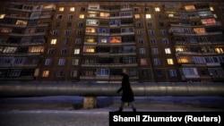 Советтік үлгідегі көпқабатты үйдің жанынан өтіп бара жатқан адам