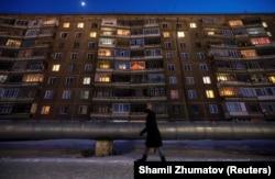 Женщина идет на фоне панельного жилого дома советской постройки.
