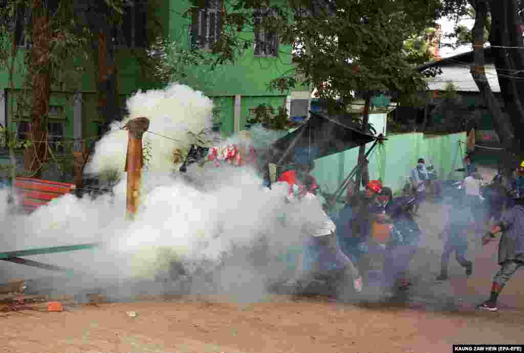 Демонстранттар аскердик төңкөрүшкө каршы нааразылык жыйыны учурунда полиция аткан көздөн жаш агызган газдын айынан качууда. Мандалай шаары, Бирма. 2021-жылдын 20-февралы.