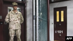 A guard stands inside a doorway at Camp 6 detention facility at Guantanamo Bay.