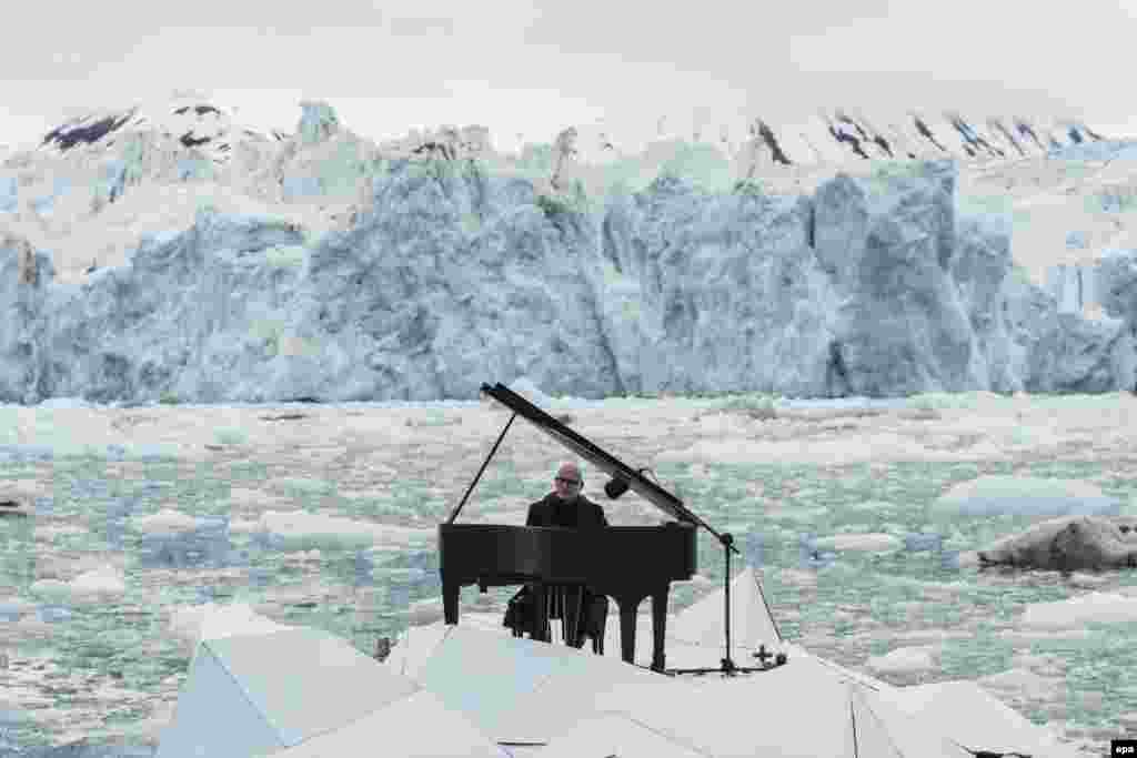 A handout image released by Greenpeace shows Italian pianist Ludovico Einaudi playing the piano during a concert in front of the Wahlenbergbreen glacier in Norway on June 20. (epa/Pedro Armestre)