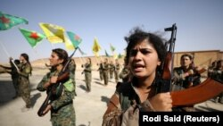 Syrian Democratic Forces (SDF) female fighters hold their weapons during a graduation ceremony in the city of Hasaka, northeastern Syria, August 9, 2017