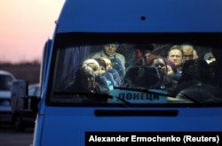 People wait in a bus to get through a checkpoint on a road linking Ukrainian government-controlled territory with a region controlled by Russia-backed separatists in Donetsk on March 13.
