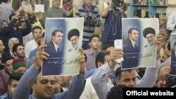 دو تن از هواداران محمود احمدینژاد پلاکاردهایی در دست دارند که روی آن نوشته شده است: «دکتر، آقا تنهاست».