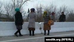 Работники бюджетных организаций в Каттакурганском районе Самаркандской области занимаются побелкой бетонных барьеров на магистральной дороге.