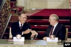 Президент США Джордж Буш — старший (слева) и советский лидер Михаил Горбачев обмениваются ручками после подписания договора СНВ в Москве в 1991 году.