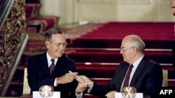 US President George Bush (L) and Soviet leader Mikhail Gorbachev exchange pens after signing the historic Strategic Arms Reduction Treaty (START) to cut the superpowers's nuclear arsenals by up to a third in Moscow, July 31, 1990