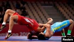 Казахстанский борец греко-римского стиля Алмат Кебиспаев (в синей форме) в поединке с атлетом из Тайбэя. Джакарта, 21 августа 2018 года.
