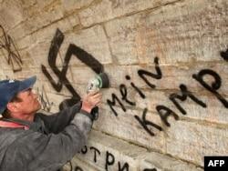 Человек стирает нацисткие надписи и свастику на стене в Павловском дворцовом комплексе за Санкт-Петербургом. Иллюстративное фото.