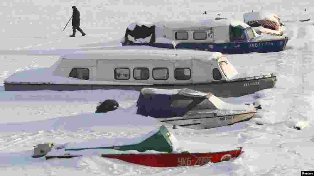 A man passes by snow covered boats in the Ukrainian capital, Kyiv, on February 10. (REUTERS/Anatolii Stepanov)