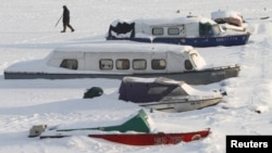 A man passes by snow-covered boats during the current cold spell in Kyiv.