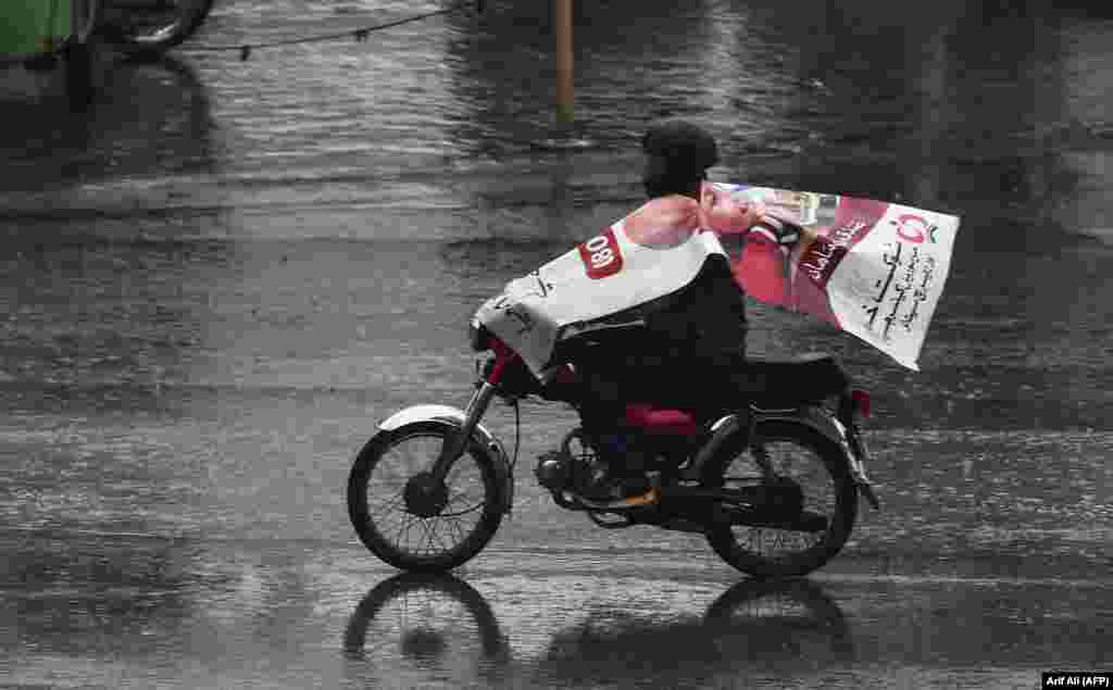 A Pakistani man wears a poster to protect himself from rain as he rides a motorbike in Lahore. (AFP/Arif Ali)