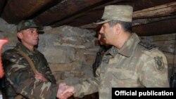 Zakir Həsənov (sağda) əsgərlə görüşür.
