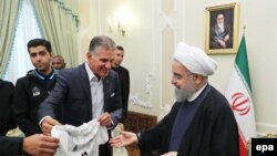 Iranian president Hassan Rohani (R) receives a jersey from Iranian national soccer team's Portuguese head coach Carlos Queiroz (L) during a reception at the presidential office in Tehran, June 14, 2017