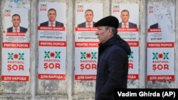 A man walks past election posters in Chisinau a day ahead of the February 24 Moldovan elections.