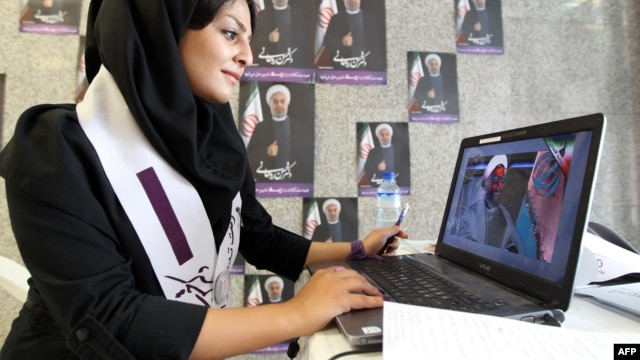 A supporter of President-elect Hassan Rohani works on her laptop in one of his campaign offices in Tehran before the June 14 vote.