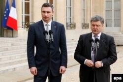 Vitali Klitschko (solda) petro Poroshenko ilə birgə Parisdə Fransa prezidenti ilə görüşdən sonra jurnalistlərlə söhbət edərkən. 7 may 2014