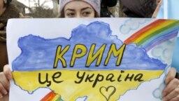 Девушка с плакатом с надписью на украинском языке: «Крым — это Украина» — во время акции в Симферополе против агрессии России, незадолго до аннексии полуострова. 10 марта 2014 года.