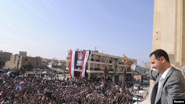 Syrian President Bashar al-Assad greets the crowd during a visit to Raqqa on November 6.