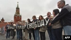 "Human rights activist Natalya Gorbanevskaya (4th from left) attends a memorial protest action on Red Square in Moscow on August 25, 2013, with the banner ""For your freedom and ours."""