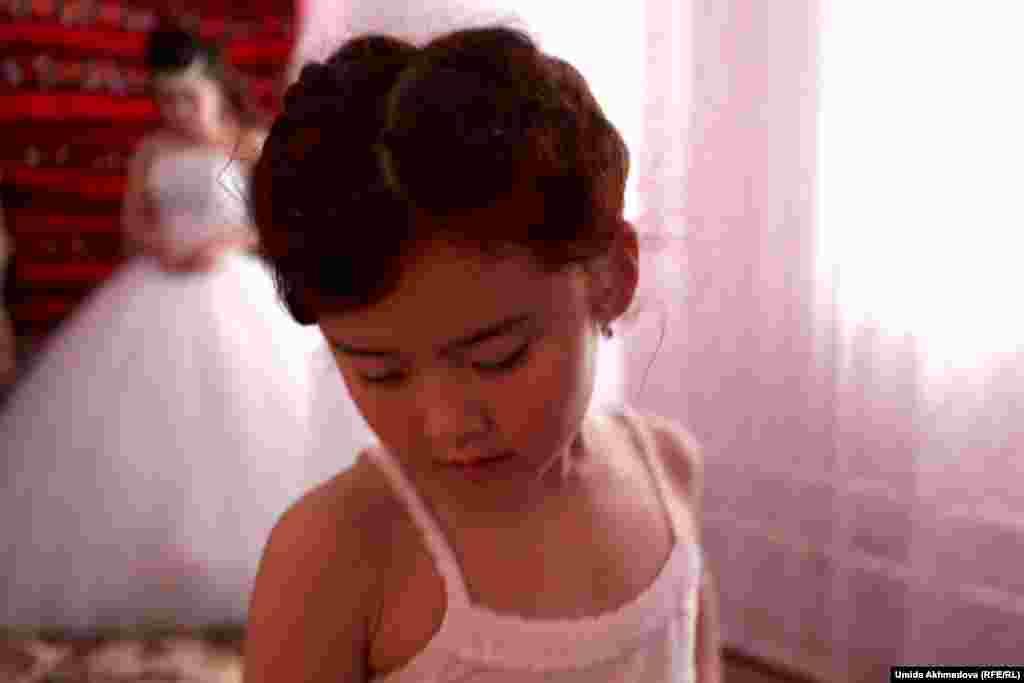 В день свадьбы в доме жениха Аякоз решила подготовиться к торжеству заранее. Ранним утром Аякоз уехала в Газалкент, чтобы сделать прическу и макияж. К свадьбе готовится не только невеста, но и ее родственники. На этом фото к торжеству одевают маленькую родственницу Аякоз.