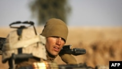 A U.S. Marine gears up for a mission northeast of Marjah in Helmand Province.