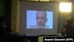 Pakistani journalists watch a video showing Indian national Kulbhushan Jadhav, convicted of espionage, during a press conference in late March.