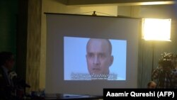 Pakistani journalists watch a video showing Indian national Kulbhushan Jadhav, arrested on suspicion of spying, during a press conference in Islamabad in March 2016.