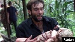 Доброволец несет раненого ребенка - после штурма здания школы в Беслане, 3 сентября 2004 года