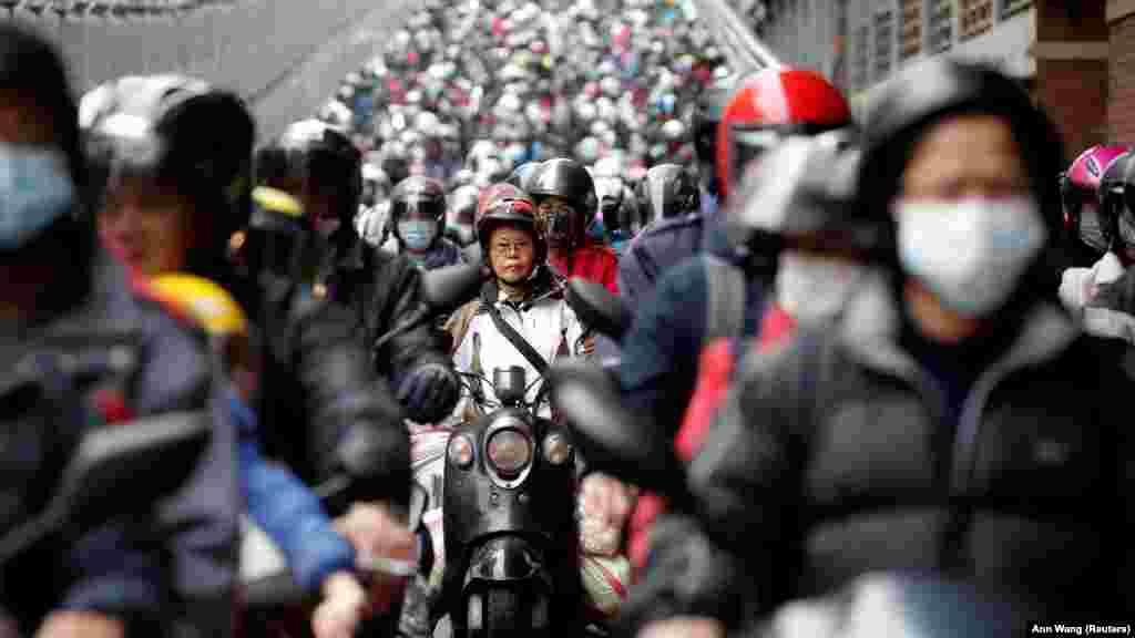 Маска тағып, мотоцикл мінген жолаушылар таңертең жұмысқа бара жатыр. Тайвань.