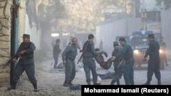 Afghan police carry away a victim after a blast in a diplomatic zone of Kabul on October 31.